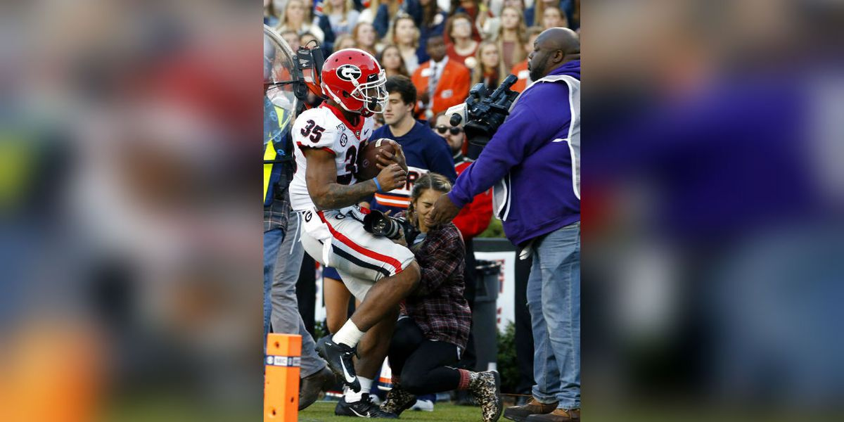Brian Herrien and Jake Fromm pray for injured photographer at halftime